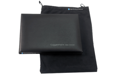 Black glove leather menu cover with blind debossed artwork and matching black suede drawstring pouch.