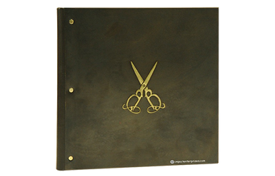 Recycled dark brass menu cover with embossed and buffed artwork.