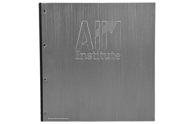 Aluminum binder cover with embossed artwork and faux leather lining on the interior.