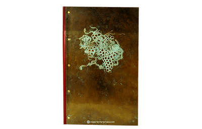 Dark brass wine list cover with light patina throughout and generic grapes artwork embossed.