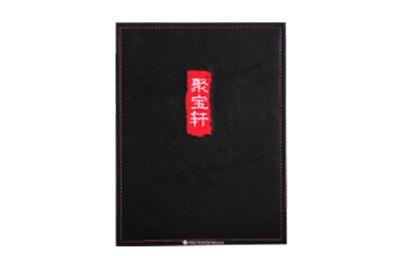 Black textured leather menu cover with embroidered artwork and red sewn edges.