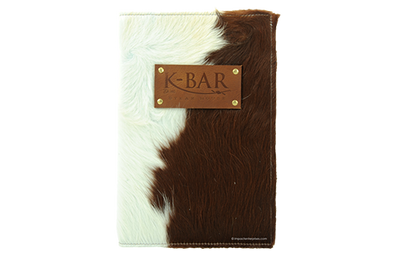 Cowhide with natural hair menu cover with blind debossed artwork on a leather patch riveted to the front.