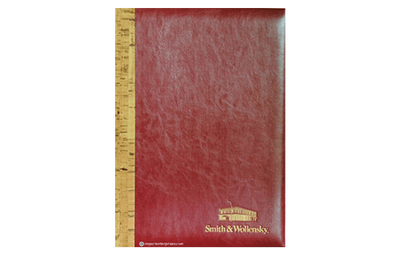 Red leather menu with cork spine and gold logo stamped in corner