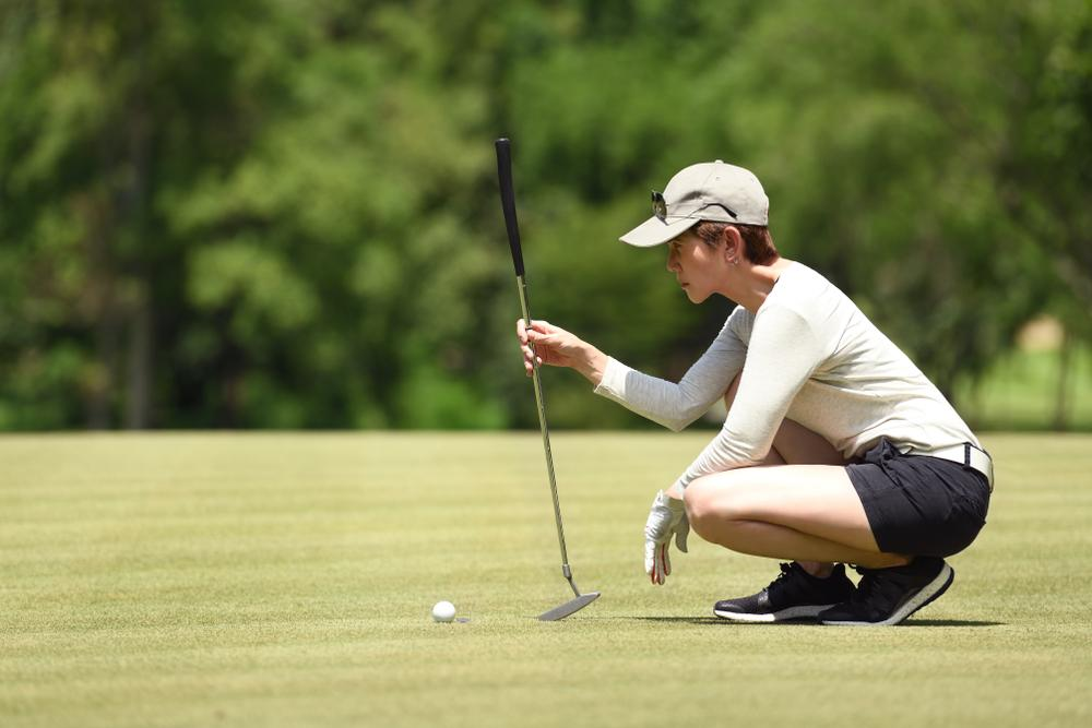 golfer looking at distance with putter to hole