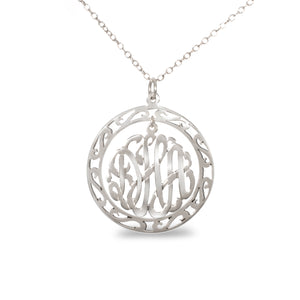 silver round monogram necklace hanging inside a hollow patterned circle pendant