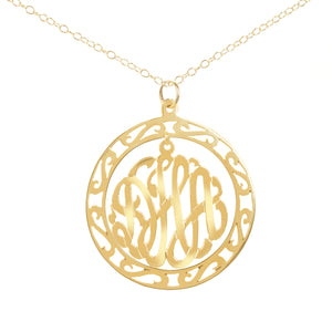 gold-plated silver round monogram necklace hanging inside a hollow patterned circle pendant