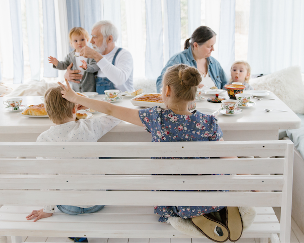 Family of four children, mother and father enjoying lunch