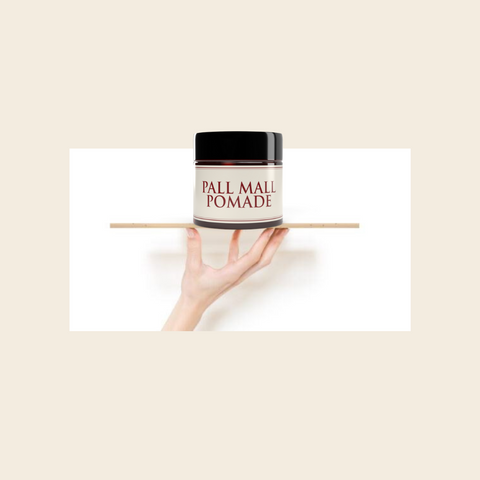 Pall Mall pomade site balanced on a piece of wood head on the fingertips of a man.m