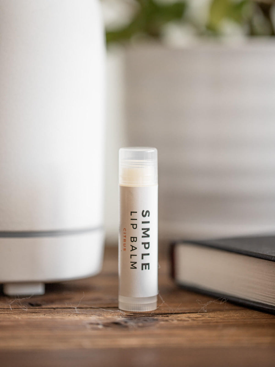 Lip balm with a diffuser, book, and plant in the background.