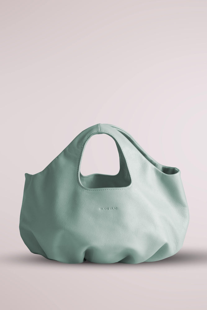 Leather mini shopper with gathering in the base. Crafted in supple calf leather and raw inner finishing without lining. Silk screened logo in white. Pillow, cloud, soft bag. Mint green butter bag Blame lilac