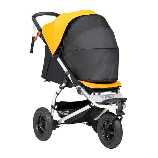 mountain buggy swift compact buggy with newborn cocoon 3/4 view shown in color gold_gold