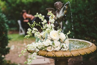 Example of Classicism - Flowers on a fountain featuring a cherub