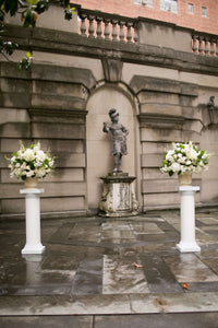Altar arrangements for DC wedding in classic whites using hydrangea, stock, and roses in urns.