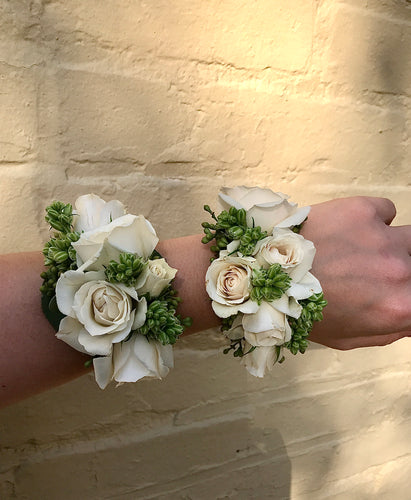 Two wrist corsages made from spray roses and texture, against a yellow brick wall.