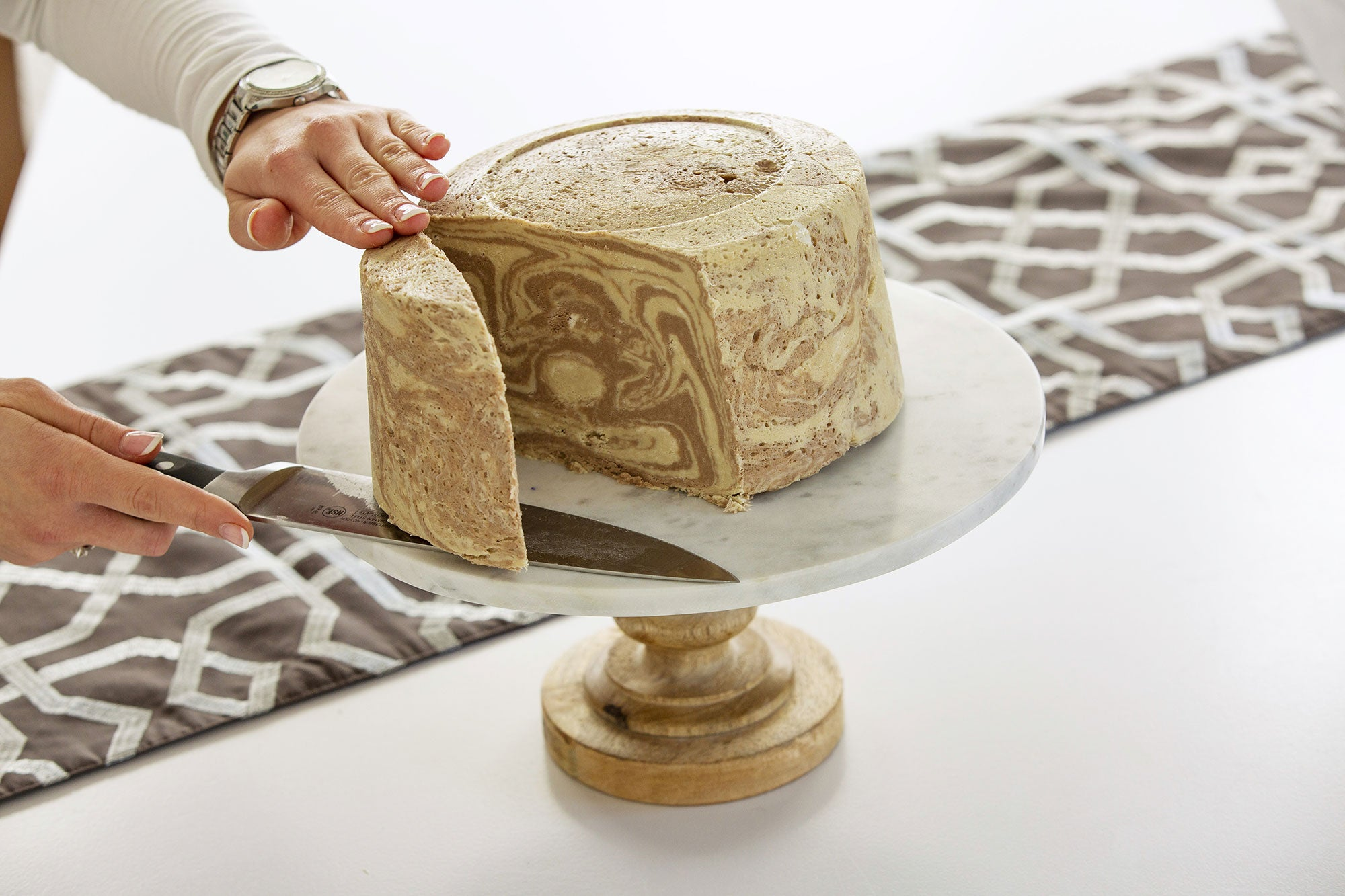 Slicing a piece of marble halva cake