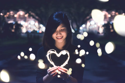 Japanese women holding a  heart that is lit up