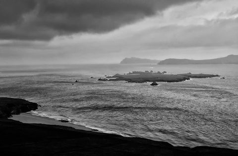 A thunderous cloud looking down on the sea with an island in the centre and some headlands in the background.