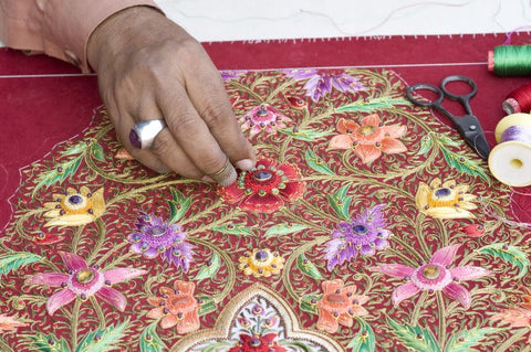BoutiquebyMariam zardozi artisan embroidering a floral tapestry.
