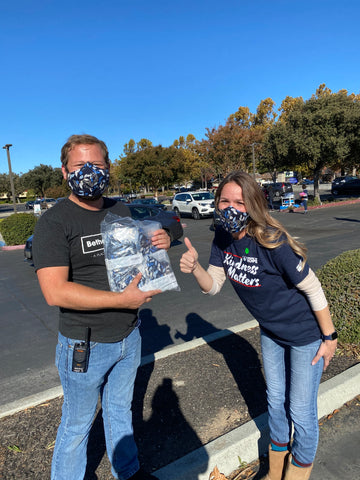 A male holding a box whole of face masks, with a lady to the right of him holding a thumbs up
