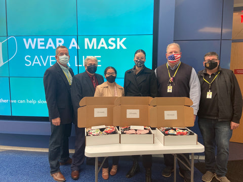 Standing in a horizontal line, there is two men to the left, two ladies in the middle, and two men to the left with face masks on. In front of them there is a white table with three open boxes with face masks in them.