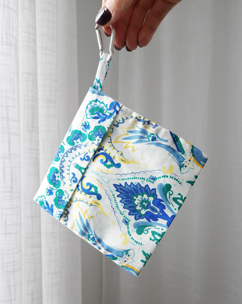 Blue floral Pouch being held with white background.