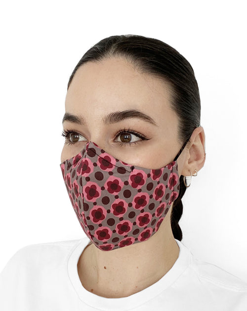 Women wearing a mask with a brown background and pink geometric shapes