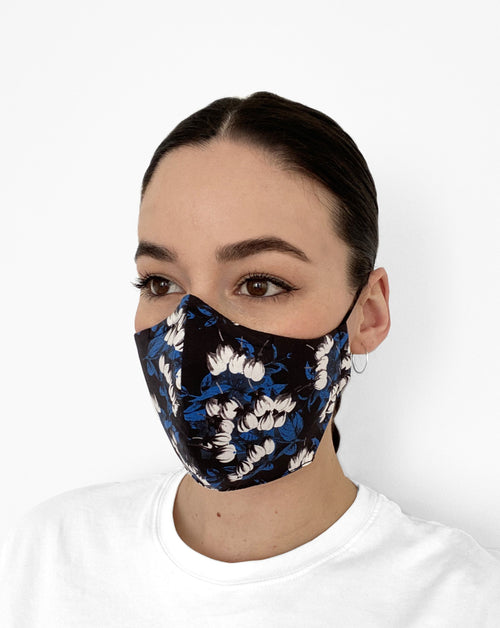 Woman wearing black mask with blue and white printed  flowers on it.