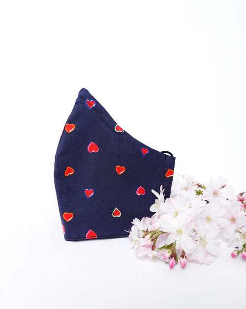 Mask with navy blue background and pink hearts all over standing in-front of pink flowers