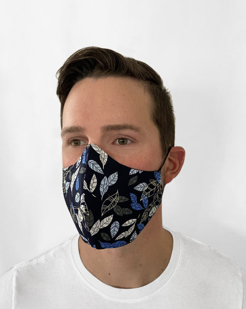 Man wearing Autumn Blue Mask. Black base color w/ blue, light blue, gray, and cream-colored autumn leaves