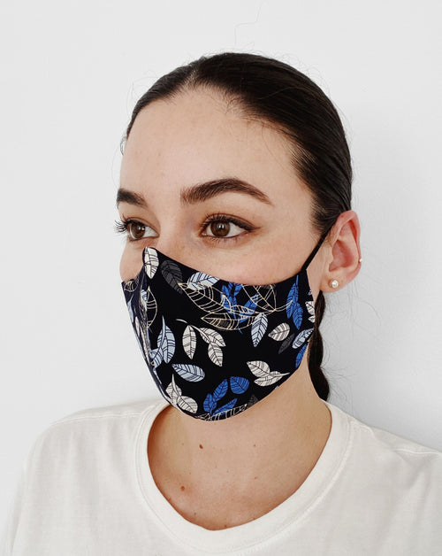 Women wearing Autumn Blue Mask. Black base color w/ blue, light blue, gray, and cream-colored autumn leaves