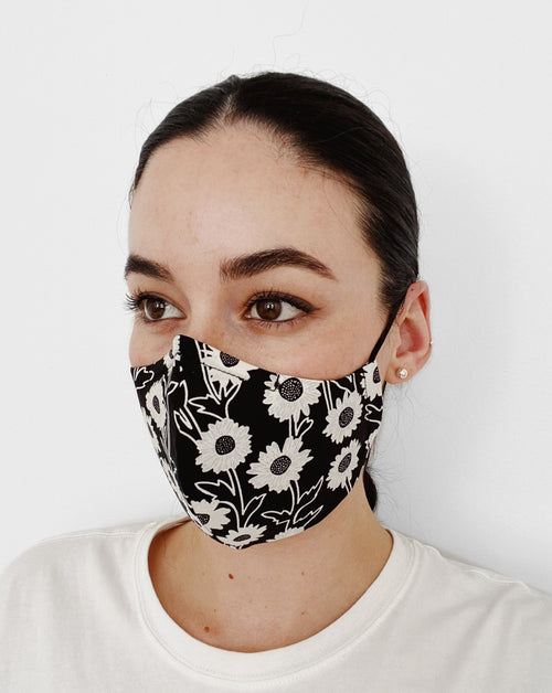 Women wearing Daisy Mask. Black base color mask w/ white daisy flower design