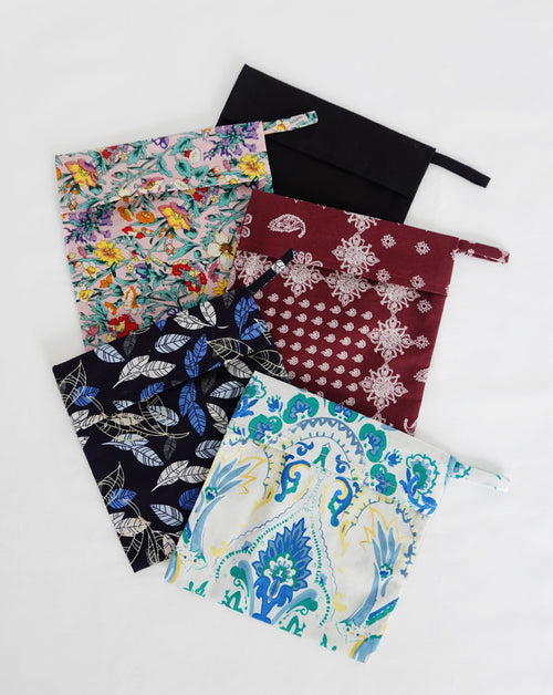 Maroon bandana pouch, mum's garden pouch, true black pouch, autumn blue pouch, and blue floral pouch all in a pile.
