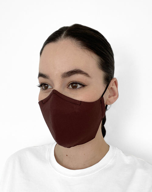 Woman wearing dark brown mask.