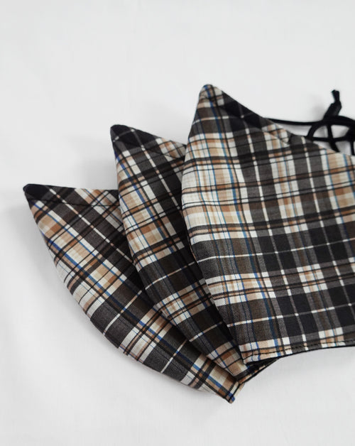 Close up image of three plaid masks with black, white, and tan colors.