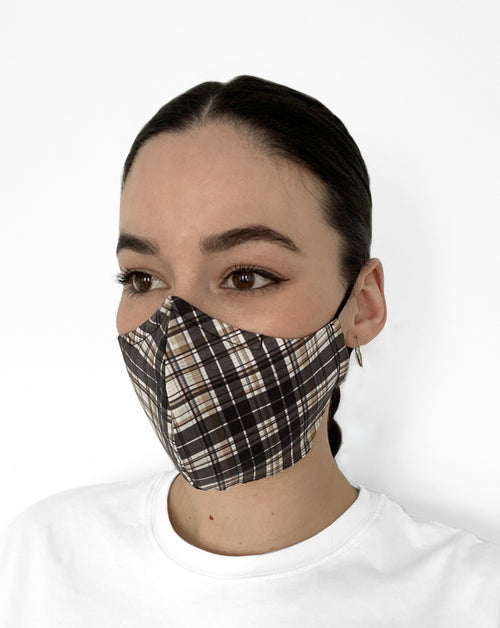 Woman wearing plaid mask with black, white, and tan colors.