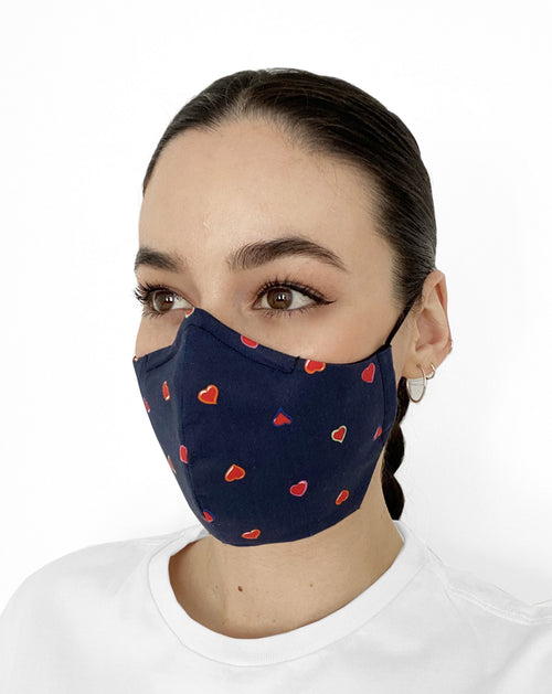 Women wearing mask with navy blue background and pink hearts all over