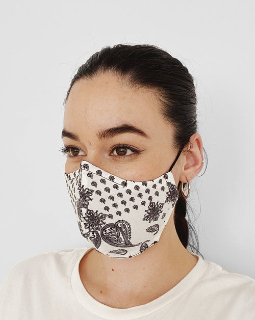 Women wearing Bandana White Mask. White base color mask w/ black colored ornament paisley design