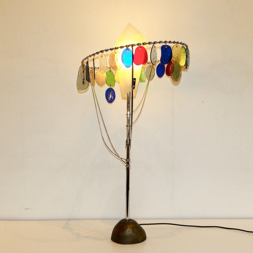 "The ""Sibari"" lamp from the Milano-Torino series by Toni Cordero was produced   in 1990.Its methacrylate lampshade is surrounded by small multicolored murano glass plaques. Its chromed metal structure ends with a free form base in bronze fusion.  /  La lampe ""Sibari"" de la série Milano-Torino de Toni Cordero qui a été produite en 1990.Son abat jour en métacrylathe est entourées de petites plaques multicolores en verre de murano. Sa structure en métal chromée se termine par une base de forme libre en fusion d"