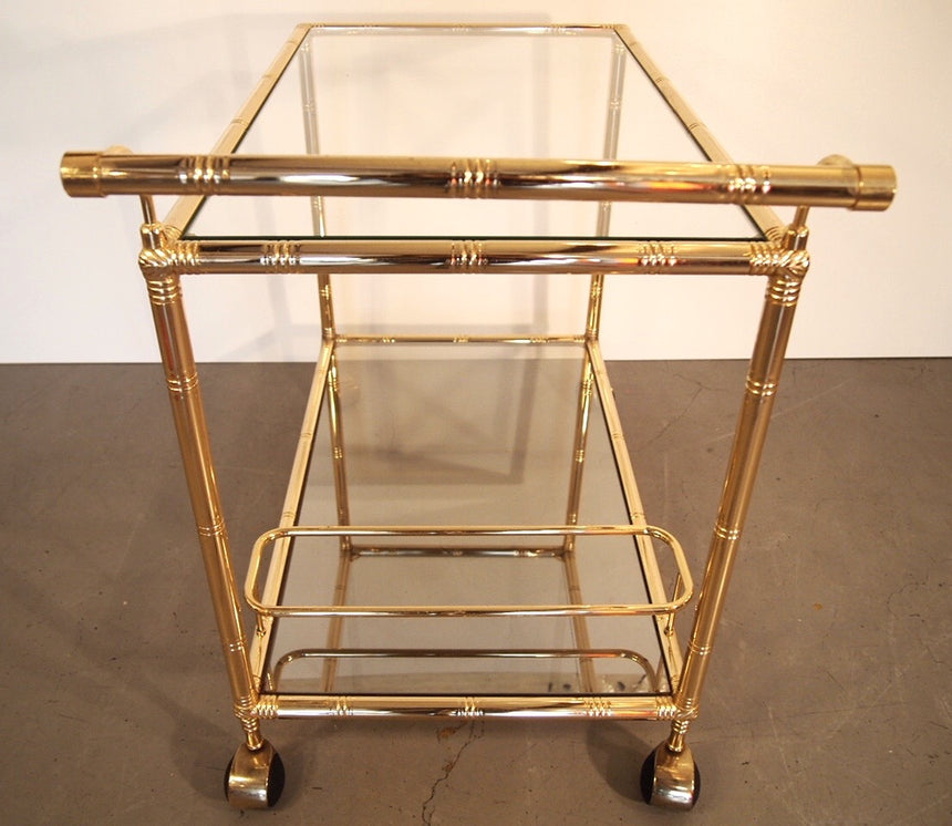 Bar cart from 1970's in brass with 2 glasses. The one below is slightly mirrored. / Desserte en laiton des années 70. La verre du bas est léger effet miroir.