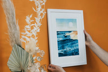 Load image into Gallery viewer, 'Golden Hour' sea shore at golden hour limited edition fine art print in white frame against orange wall