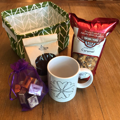Deconstructed gift basket showing fabric bin, bag of Hershey's Nuggets, BrewAble gourmet coffee, Heart Wreath mug and Caramel Popcorn