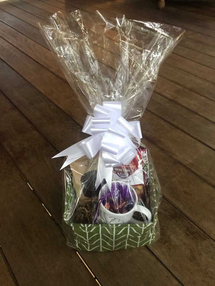 Completed gift basket wrapped in cellophane and tied with a white bow.