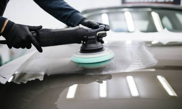 Photo of person's hands wearing black gloves holding a cut and compound hand machine overtop of the surface of a black car.