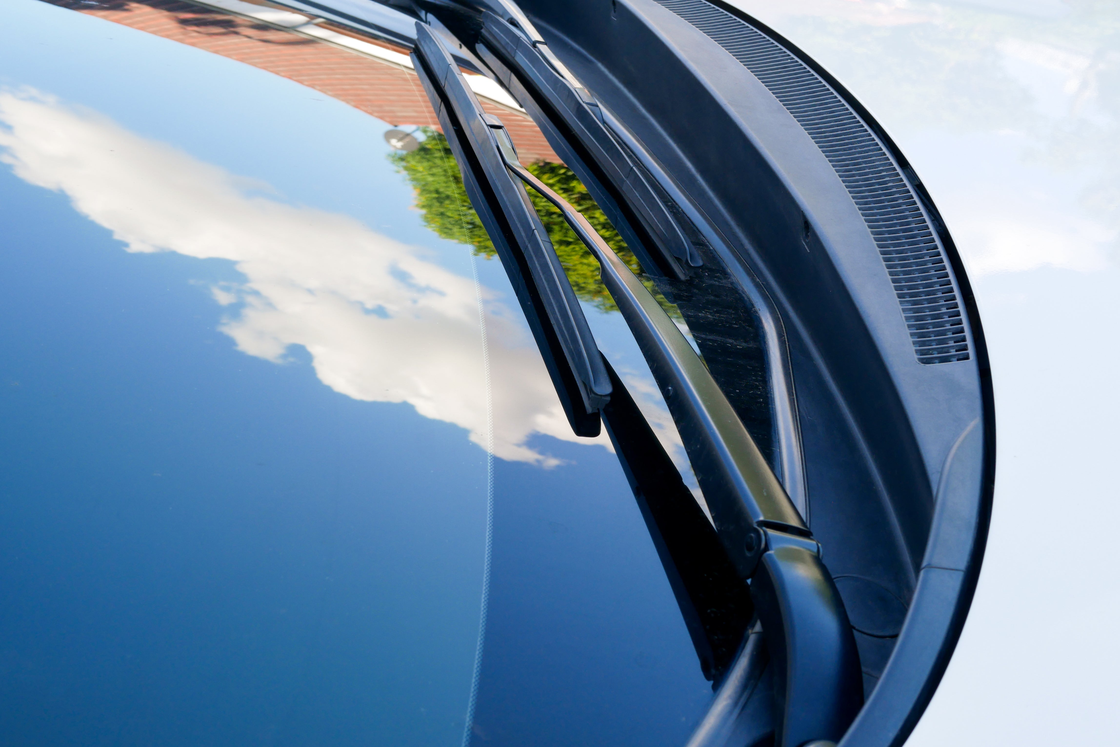 Close up of a car's windshield that is so clean the sky and clouds are perfectly reflected in it.