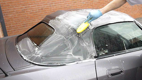 Image of a person's hand wearing a glove holding a brush and cleaning the top of a convertible grey car.