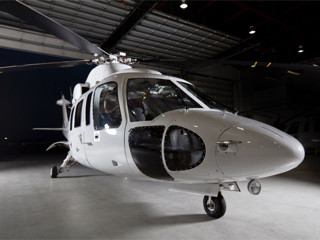 Photo of a shiny white helicopter inside an aircraft hangar.