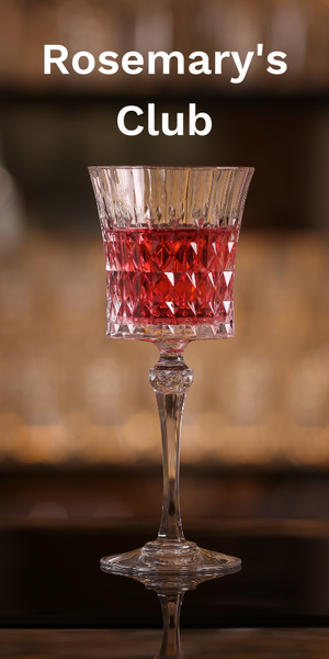 Fancy glass with red cocktail on a wooden table.