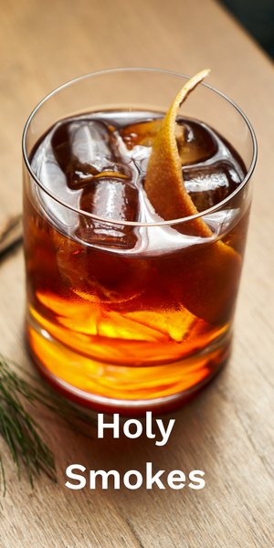 """Bourbon cocktail in a small glass on a table. Text """"Holy Smokes""""."""