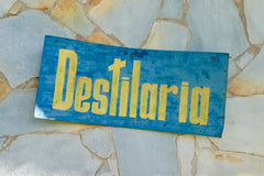 Blue sign hung on a stone wall: Destilaria, which is Spanish for Distillery