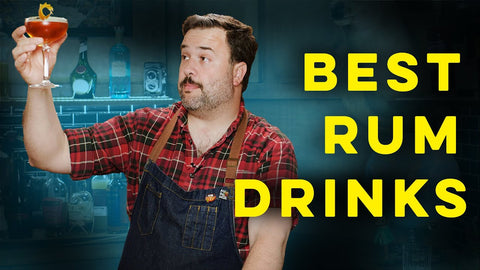 Image of a man in a work apron and a checkered shirt holding a cocktail and gazing at it against a blue green backdrop with large bright yellow text: BEST RUM DRINKS